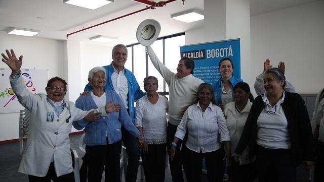 El Alcalde Enrique Peñalosa rodeado de varios adultos mayores sonriendo, beneficiarios de lo Centros días