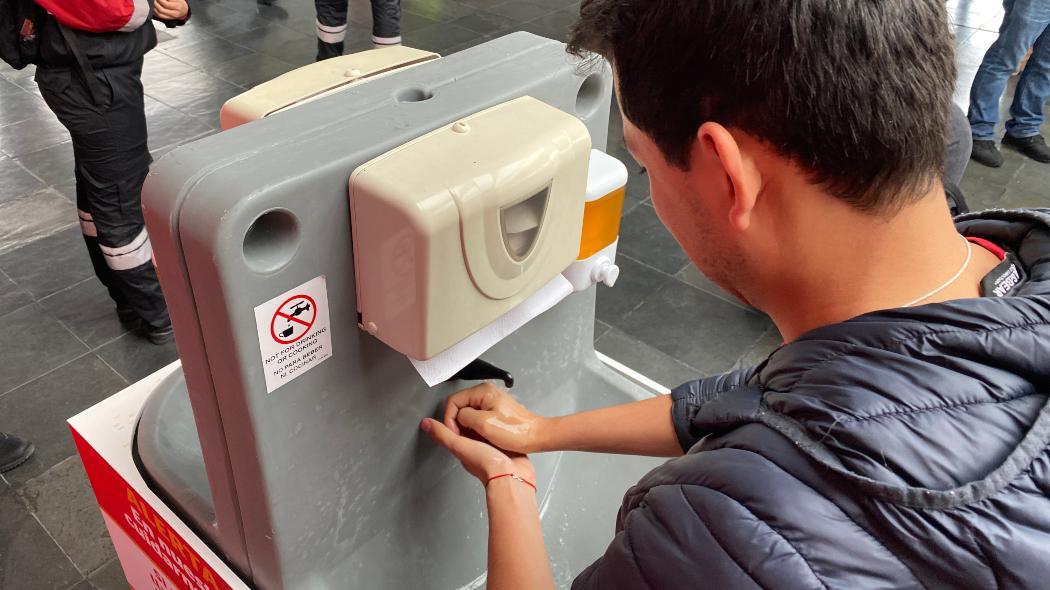 Usuario lava sus manos con agua y jabón en una estación de TransMilenio